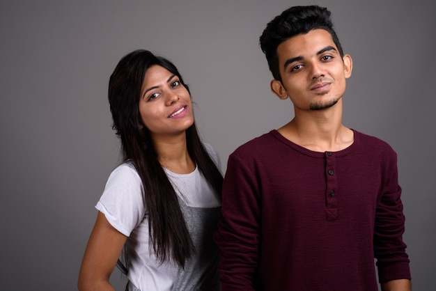 Young indian man and young indian woman together on gray wall