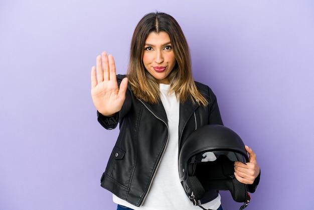 若いインドのバイクの女性は、一時停止の標識を示している手を伸ばして立って孤立し、あなたを妨げています。