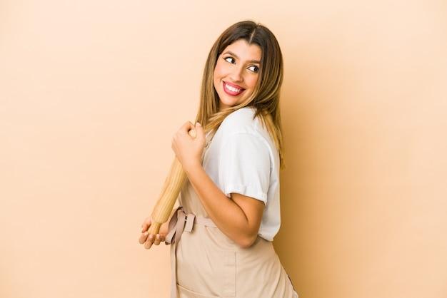 Молодая индийская изолированная женщина шеф-кондитера смотрит в сторону усмехаясь, веселая и приятная.