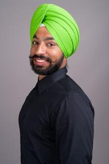 緑のターバンを身に着けている若いインドのシーク教徒の実業家