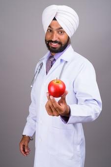 若いインドのシーク教徒の男性医師が笑顔でリンゴを持っています