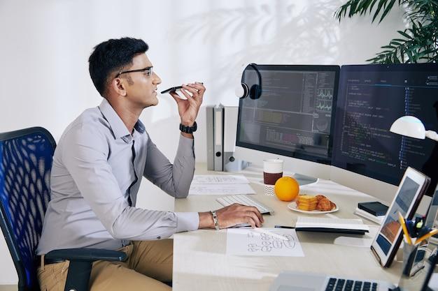 若いインドのソフトウェア開発者がコンピューター画面でプログラミングコードをチェックし、同僚に音声メッセージを録音する