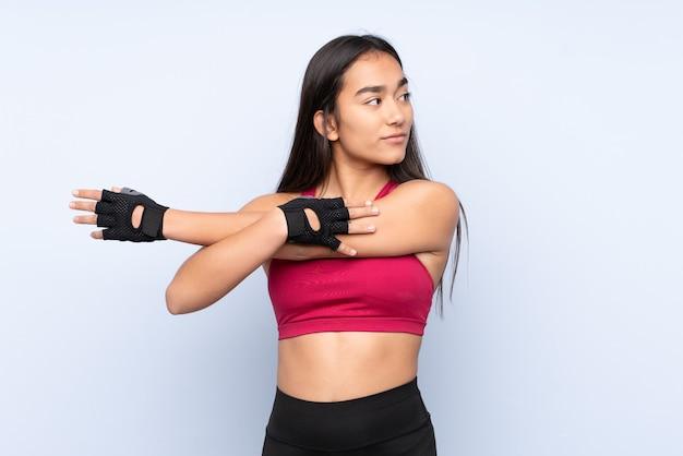 Молодая индийская спортивная женщина изолирована на синем фоне, протягивая руку