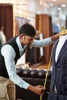 테이프와 정장 재킷의 앞을 측정하는 젊은 인도 재단사