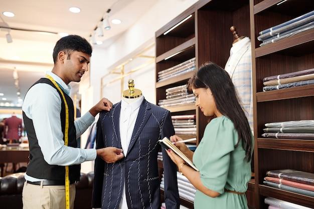 オーダーメイドのジャケットに取り組んでいて、アシスタントがプランナーでメモを取るときに詳細を測定する若いインドの仕立て屋