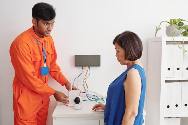 セキュリティカメラをwifiに接続し、成熟したアジアの女性にそれを使用する方法を説明する首にぶら下がっているバッジを持つ若いインドの技術者