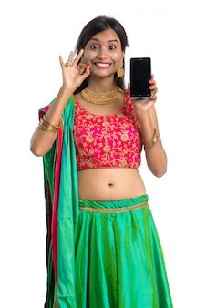 Молодая индийская традиционная девушка, используя мобильный телефон или смартфон и показывая пустой экран смартфона на белом фоне