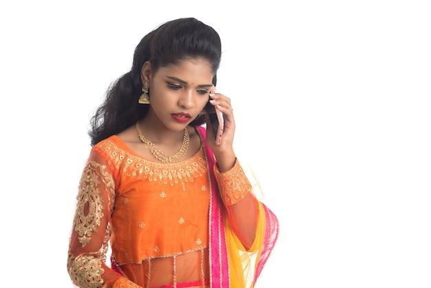 Молодая индийская традиционная девушка с помощью мобильного телефона или смартфона, изолированные на белом фоне