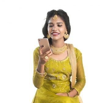 白い壁に分離された携帯電話やスマートフォンを使用して若いインドの伝統的な女の子