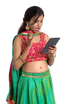 Молодая индийская традиционная девушка с помощью мобильного телефона или смартфона, изолированных на белом