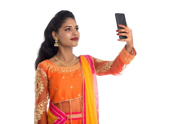 孤立した携帯電話やスマートフォンを使用して若いインドの伝統的な女の子