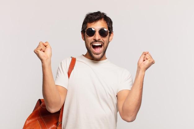 成功を祝う若いインドの旅行者の男