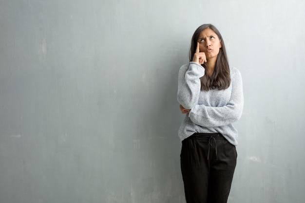 考えて見上げる、考えについて混乱しているグランジ壁に対して若いインド人女性