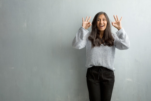 Young indian woman against a grunge wall cheerful and confident doing ok gesture, excited and screaming, concept of approval and success