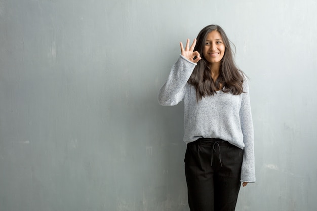 Young indian woman against a grunge wall cheerful and confident doing ok gesture