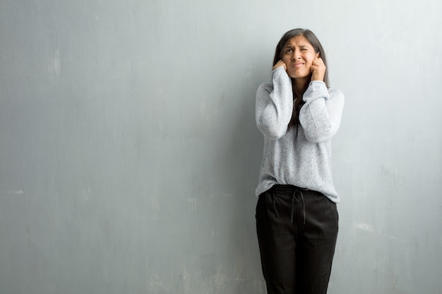 Young indian woman against a grunge wall covering ears with hands