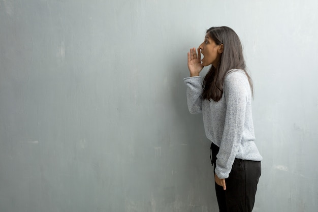 Young indian woman against a grunge wall screaming angry, expression of madness and mental instability, open mouth and half-opened eyes, madness concept