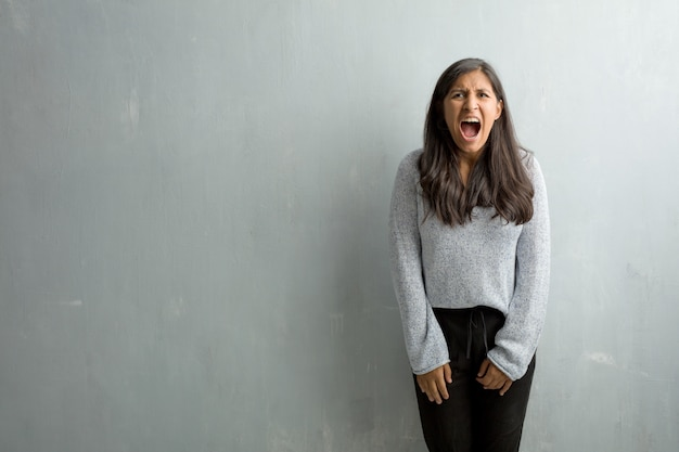 Young indian woman against a grunge wall screaming angry