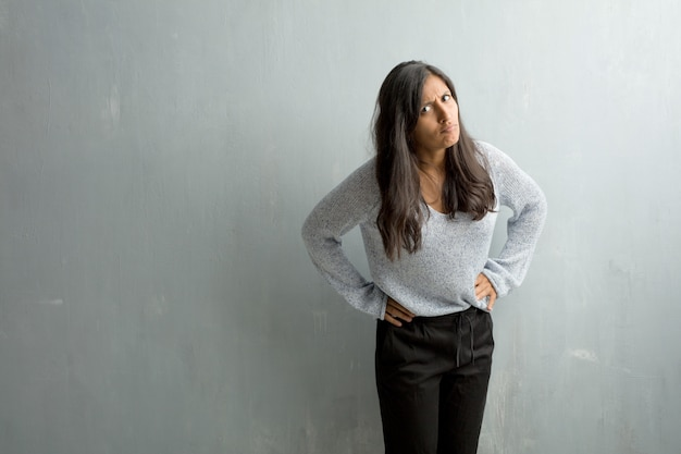 Young indian woman against a grunge wall very angry and upset, very tense, screaming furious, negative and crazy
