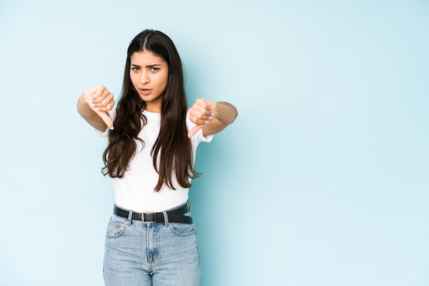 Young indian woman on blue wall showing thumb down and expressing dislike.