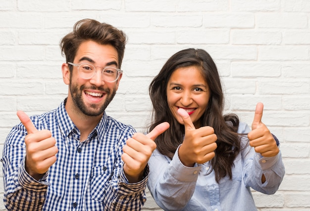Young indian woman and caucasian man couple cheerful and excited, smiling and raising her thumb up, concept of success and approval, ok gesture