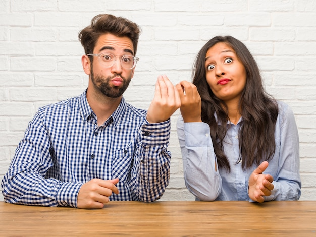 Young indian woman and caucasian man couple doing a typical italian gesture
