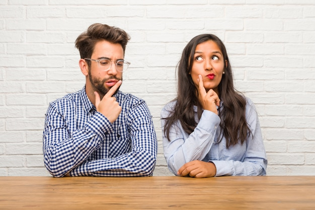 Young indian woman and caucasian man couple doubting and confused