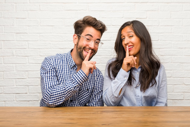 Young indian woman and caucasian man couple keeping a secret or asking for silence