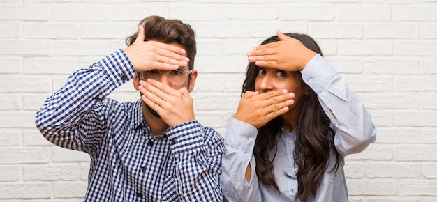 Young indian woman and caucasian man couple looking through a gap, hiding and squinting