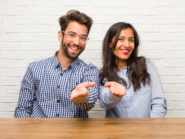 Young indian woman and caucasian man couple reaching out to greet someone or gesturing to help, happy and excited