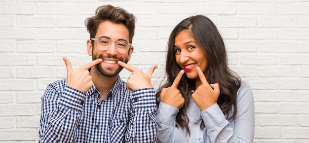 Young indian woman and caucasian man couple smiles, pointing mouth, concept of perfect teeth, white teeth, has a cheerful and jovial attitude