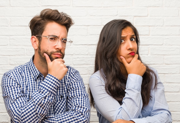 Young indian woman and caucasian man couple thinking and looking up, confused about an idea