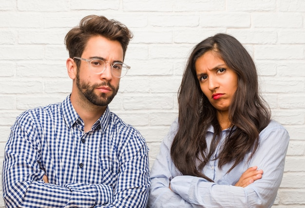 Young indian woman and caucasian man couple very angry and upset, very tense