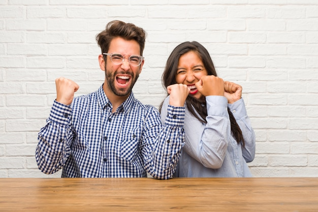 Young indian woman and caucasian man couple very happy and excited, raising arms