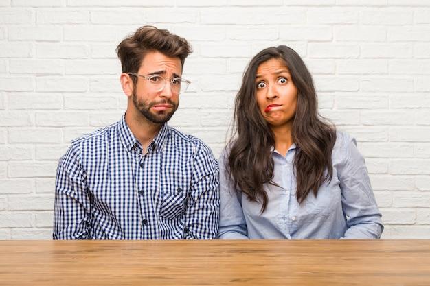 Young indian woman and caucasian man couple worried and overwhelmed, forgetful, realize something, expression of shock at having made a mistake