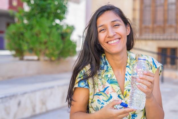 거리에서 물을 driking 젊은 인도 여자