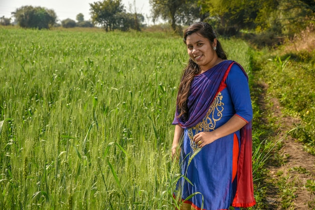A young indian woman farmer working in the wheat farm field.