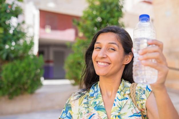 거리에서 물 한 병을 들고 젊은 인도 여자