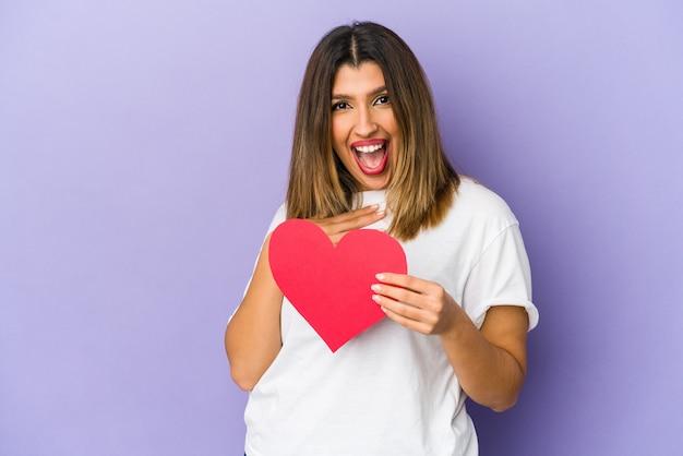 孤立したバレンタインデーの心を持っている若いインドの女性は、胸に手を置いて大声で笑います。