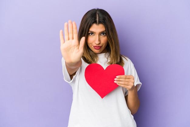 발렌타인 데이 심장을 들고 젊은 인도 여자는 당신을 방지, 정지 신호를 보여주는 뻗은 손으로 서 고립.