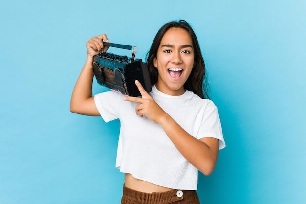Молодая индийская женщина, держащая винтажную кассету изолирована