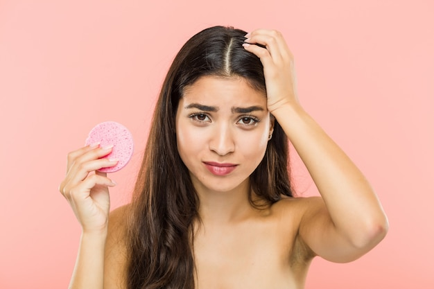Young indian woman holding a facial skin care disc being shocked, she has remembered important meeting.