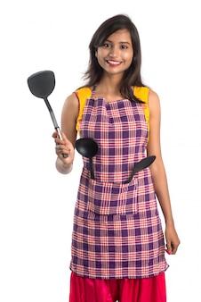 白い背景の上の台所用品(スプーン、ステープラ、鍋、鍋など)を保持している若いインド人女性