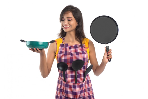 Молодая индийская женщина, держащая кухонные принадлежности (ложка, скоба, ковш и сковороду и т. д.) на белом фоне
