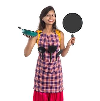 Молодая индийская женщина, держащая кухонную утварь (ложка, степула, ковш, сковорода и т. д.) на белом фоне