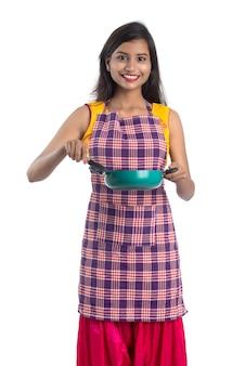 흰색 배경에 주방기구 (숟가락, stapula, 국자, 팬 등)을 들고 젊은 인도 여자