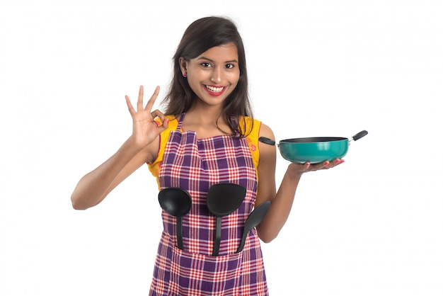 Young indian woman holding kitchen utensil (spoon, stapula, ladle, and pan, etc.) on a white space