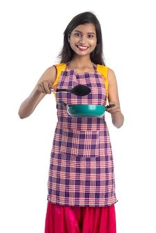 주방기구를 들고 젊은 인도 여자