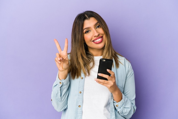 Young indian woman holding a phone showing number two with fingers.