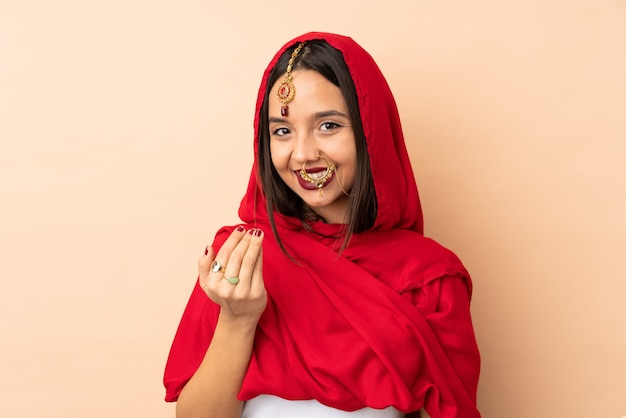 Young indian woman isolated on beige inviting to come with hand. happy that you came